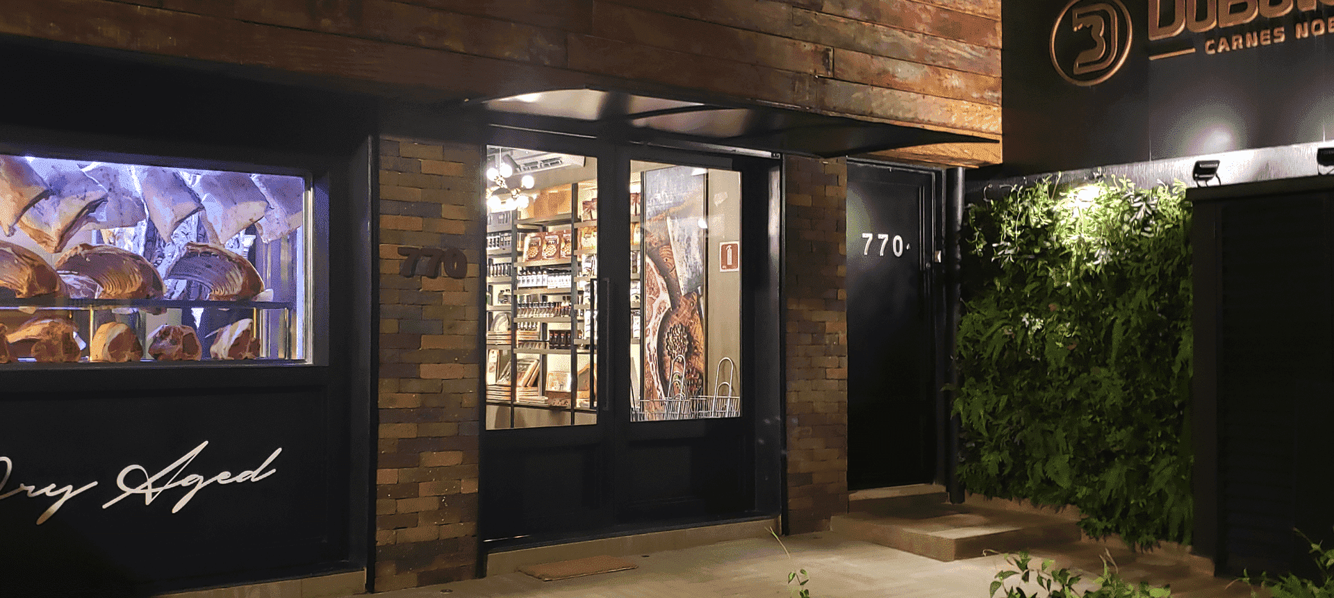 Imagem de uma fachada de loja em madeira. No canto esquerdo observa-se uma vitrine com diversas peças de carne na vitrine dry aged.
